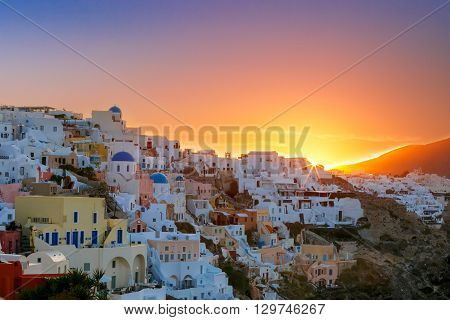 Old Town of Oia on the island Santorini, white houses and church with blue domes at sunrise, Greece