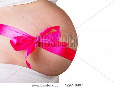 Pregnant woman with red bow on her stomach in anticipation of a girl isolated on white background.