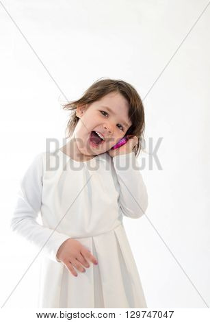 Sweet girl amazed screaming at toy phone on white