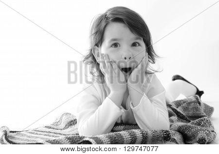 Sweet girl amazed sit on colored blanket isolated on white