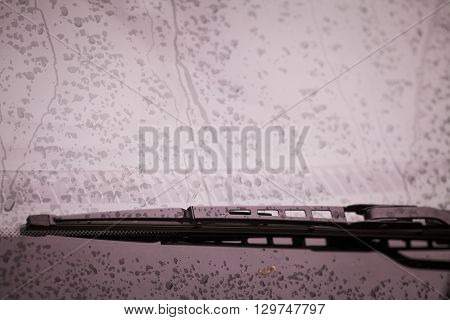 Color image of the wipers of a car with rain drops on the windshield.