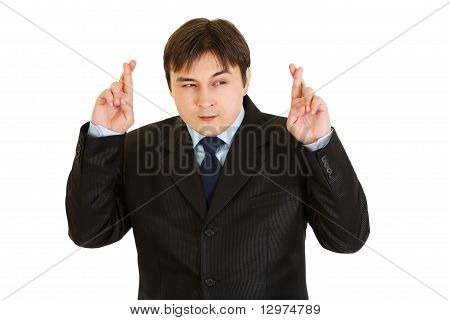 Superstitious young businessman holding crossed fingers isolated on white