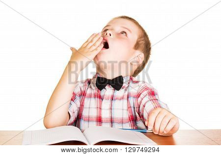 Yawning boy sitting at notebook isolated on white background.