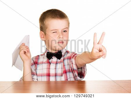 Boy with paper plane sitting at a table isolated on white background.
