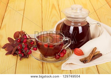 Jug and cup of rosehip drink, vanilla sticks on a background of light wood.