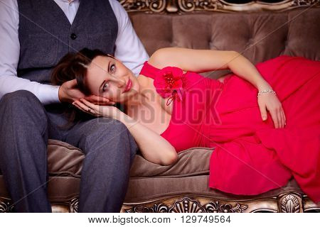A pregnant woman lies in her husband's lap. She put her head on his palm. Wife in red and her husband in a jacket