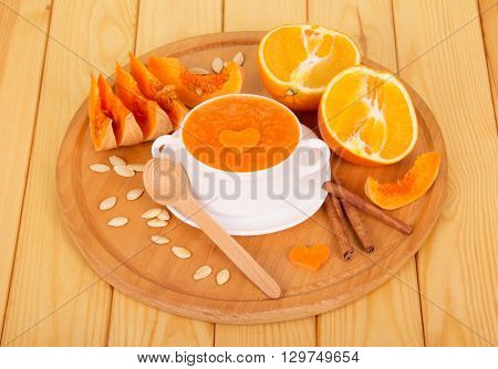 Pumpkin puree in a white tureen, sliced orange and vanilla sticks on a light wooden planks.