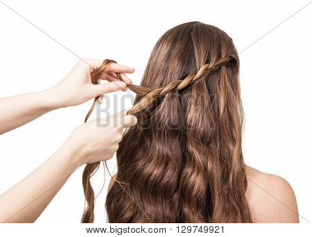 Hands hairdresser braided lock of the girl with long hair isolated on white yone.