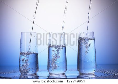 Drinking Glasses With Reflection In Drops. Water Pouring