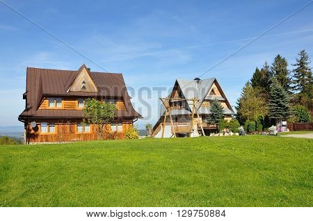 Two private houses with pitched roof in Zakopane style on a background of green grass and blue sky.