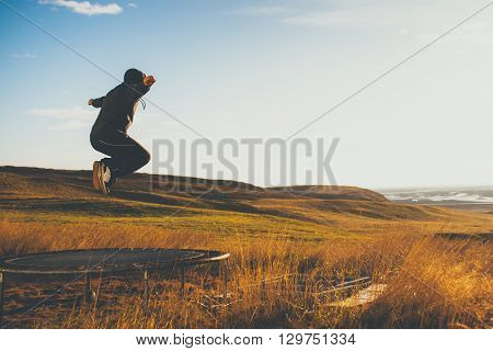 Man on trampoline in Iceland. Concept of freedom and loneliness.