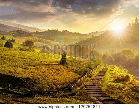Steps Down To Village In Foggy Mountains At Sunset