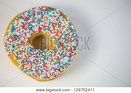 fresh doughnut with sprinkles, on white background