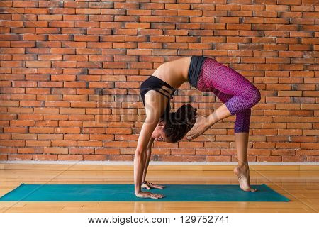 Woman practicing yoga against a brick wall
