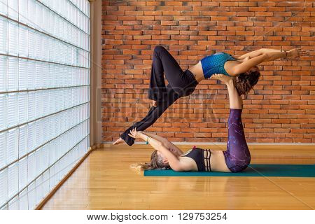 Two women practice acroyoga, showing friendship, trust and strengh.