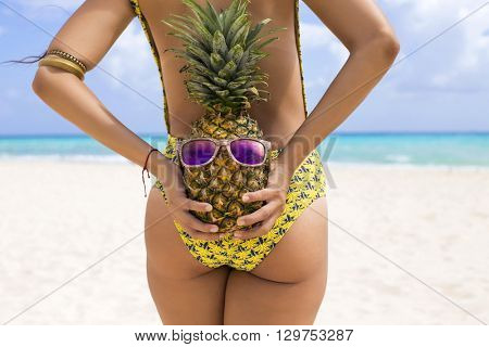 Woman on the Caribbean holding a pineapple with sunglasses