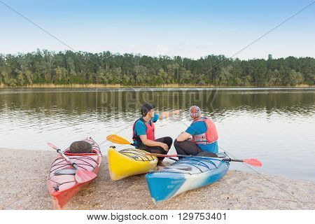 Men travel by canoe on the river in the summer a sunny day.