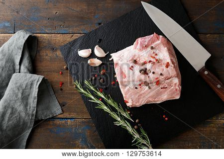 Piece Of Raw Pork, A Knife And Ingredients For Cooking On Black Slate