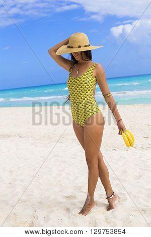 Young woman holding bananas at the beach. Playa del Carmen, Mexico.