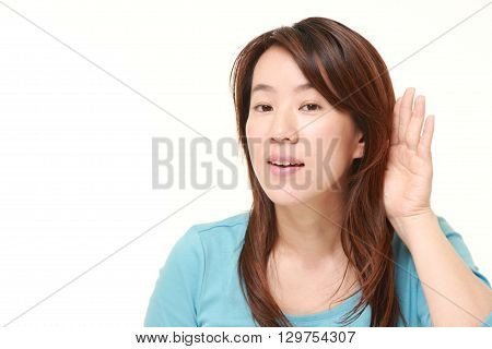 portrait of woman with hand behind ear listening closely on white background