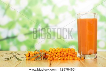 Bunch of sea buckthorn and a glass of juice from its berries on abstract green background.