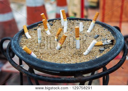 Smoked Cigarettes Butts in a Dirty Ashtray Big Bin. Life concept