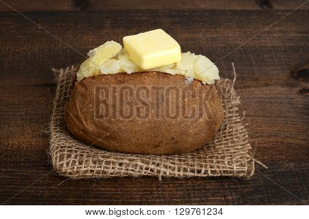 closeup of baked potato with butter on burlap