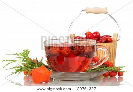 Rosehip berries, mountain ash and cup of tea isolated on white background.