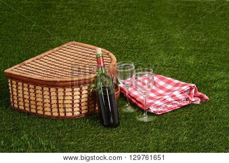 picnic basket with wine on grass with blanket