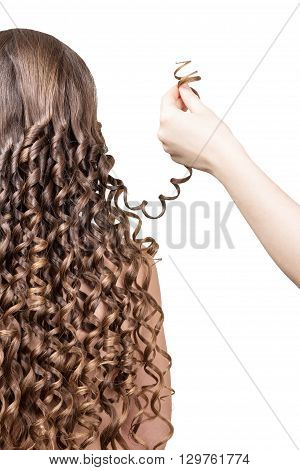 Female hand holding a lock of curly girl isolated on white background.
