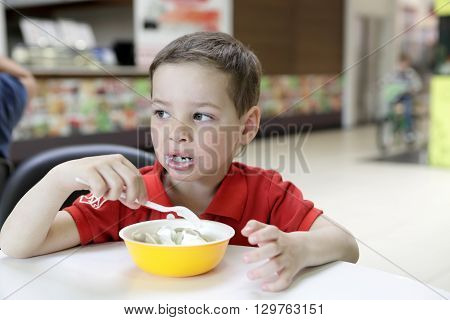 Kid eating meat dumplings with sour cream in cafe