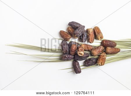 Many dates placed on a palm leaf on white background.
