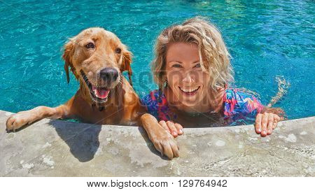 poster of Funny portrait of smiling woman playing with dog and training golden retriever puppy in blue swimming pool. Popular dog breeds outdoor activity and fun games with family pet on summer beach holiday.