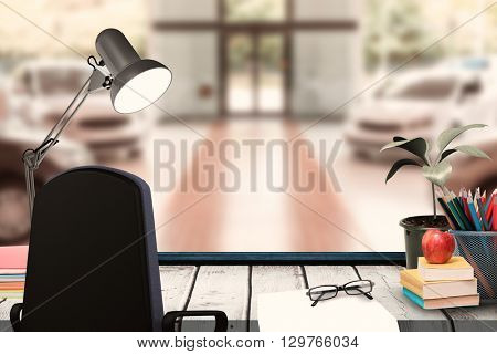 A desk with lamp and documents against view of row new car