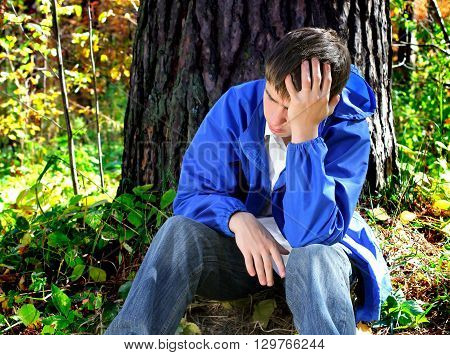 Sad Young Man in the sit in the Forest