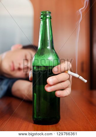 Tired Young Man sleep with Bottle of the Beer and Cigarette at the Home