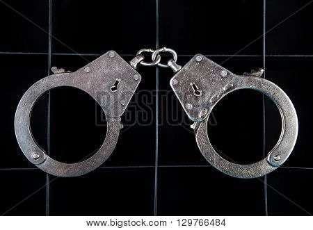 The Handcuffs on the Black Background closeup
