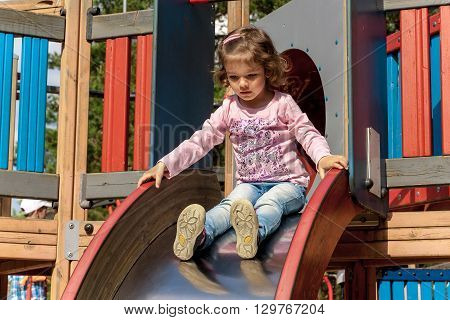 The child is preparing for the slide on the hill