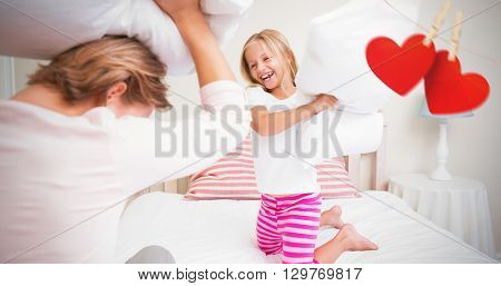 Composite image of mother and daughter fighting with pillows on a bed