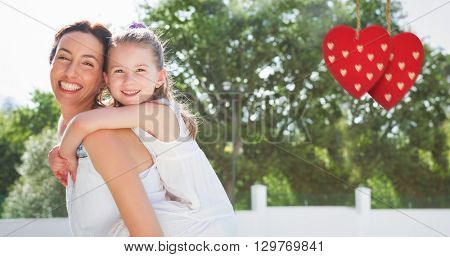 Composite image of mother and daughter holding each other on garden