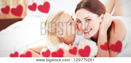 Cute little girl kissing her mother against hearts hanging on a line