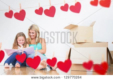 Mother and daughter reading a book against hearts hanging on a line