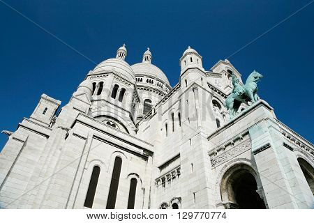 the catholic church Basilica of Sacre Coeur or Sacred Heart with dome and statue of King Saint Louis public monument landmark from year 1914 in Montmartre Paris France Europe