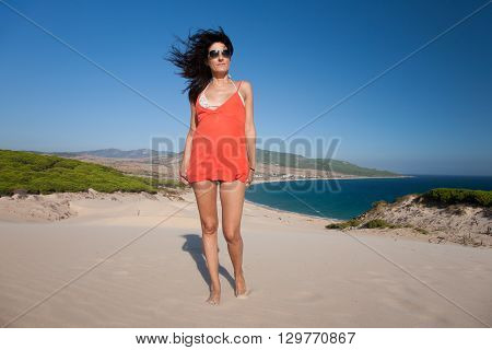 brunette summer vacation woman with sunglasses bikini and orange shirt dress standing posing on sand dune looking with blue sky in Bolonia beach in Tarifa Cadiz Andalusia Spain Europe