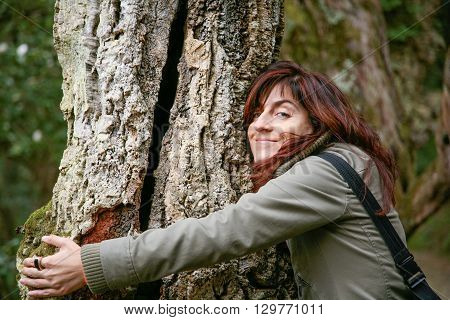 woman green jacket laughing looking hugging or embraced a trunk tree in a forest or park
