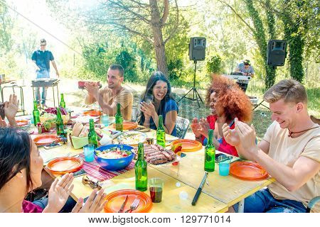 group of young people at barbecue in garden sitting at the table having fun talking and laughing