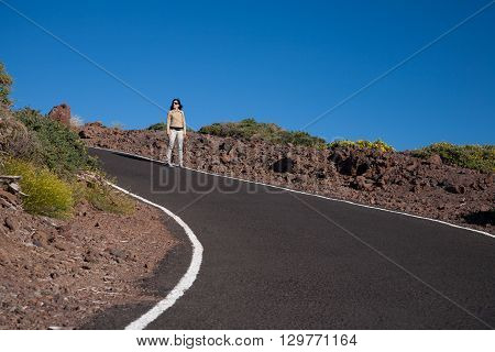 brunette woman brown jacket white trousers standing in curve of rural grey road with blue sky of La Palma Canary Islands Spain Europe
