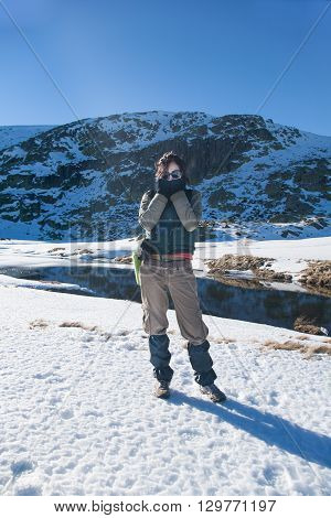 sport active woman with green vest brown trousers standing in snow looking hands gloves in face with cold blue sky in Gredos mountain Avila Spain Europe