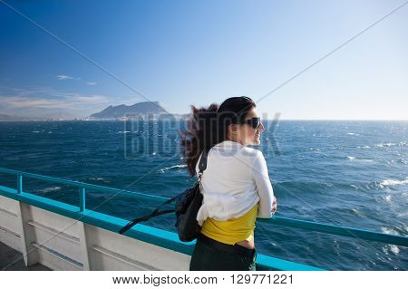 woman white and yellow clothes leaning on boat railing in ferry in Mediterranean sea Strait of Gibraltar with the Rock in the background in Cadiz Andalusia Spain Europe