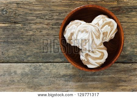 Soft delicious zephyr in a wooden bowl on the old wooden background. Space for text. Top view